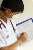 Un doctor repasa la carta de los patientâs EKG Foto de archivo