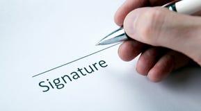 Un document avec un endroit pour une signature et une main des WI d'un homme Photo stock