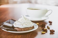 Un dolce con la crema della chiara dell'uovo, pezzi di cioccolato, anice, cardamomo e una tazza di caffè caldo su una tavola di l immagine stock