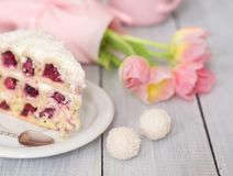Un dolce con le ciliege ed i tulipani rosa sulla tavola di legno bianca Fotografie Stock