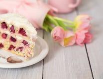 Un dolce con le ciliege ed i tulipani rosa sulla tavola di legno bianca Fotografia Stock