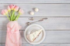 Un dolce con le ciliege ed i tulipani rosa sulla tavola di legno bianca Immagini Stock Libere da Diritti