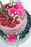 Un dolce del gocciolamento di colore di nozze con le rose, i mirtilli ed i lamponi Fotografia Stock