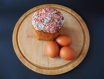 Un dolce di pasqua con tre uova sul bordo di legno fotografia stock