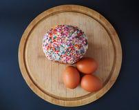 Un dolce di pasqua con tre uova sulla cima del bordo di legno fotografia stock