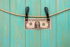 Un dollar accrochant sur une corde avec des pinces à linge image libre de droits