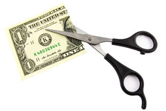 Un dollar coupé dans la moitié avec des ciseaux Photos stock