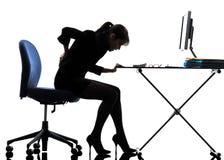 Silueta del dolor del dolor de espalda de la mujer de negocios que se sienta Fotografía de archivo libre de regalías
