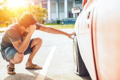 Un dolor de cabeza del hombre cuando avería del coche y neumático desinflado de la rueda en el camino en el estacionamiento foto de archivo libre de regalías