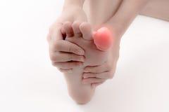 Un dolor en el dedo del pie aislado en el blanco, concepto del dolor Imagen de archivo