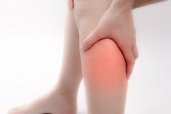 Un dolor en una pierna asiática adentro aislada en el fondo blanco Foto de archivo