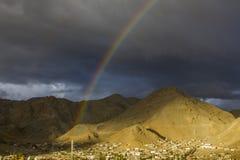 Un doppio arcobaleno nel cielo uguagliante scuro sopra il villaggio in una valle del deserto della montagna fotografie stock libere da diritti