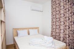 Un dormitorio en estilo minimalista con una cama y un guardarropa Imagen de archivo libre de regalías