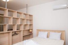 Un dormitorio en estilo minimalista con una cama y un guardarropa Fotos de archivo libres de regalías