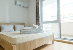 Un dormitorio en estilo minimalista con una cama y un guardarropa Foto de archivo libre de regalías