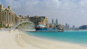 Un dragueur pompe le sable pour former une île en forme de paume Photographie stock