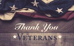 Un drapeau américain ou une étamine sur un fond en bois avec la salutation de jour du ` s de vétéran photos stock