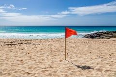 Un drapeau d'avertissement sur une plage images libres de droits