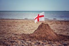 Un drapeau de l'Angleterre sur un château de sable sur une plage britannique images libres de droits
