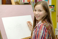 Un drenaje joven sonriente de la muchacha del artista Foto de archivo