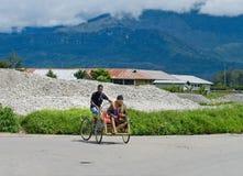 Un driver del trishaw sulla via La Nuova Guinea Fotografia Stock
