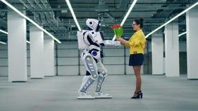 Un droid da un ramo de tulipanes rojos a una mujer y ella lo abraza almacen de metraje de vídeo