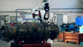Un droid utiliza un arma del tornillo, trabajando con un detalle del metal en una fábrica almacen de metraje de vídeo