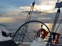 Un dueño de un yate que funciona con un yate de la navegación que deja una tormenta en el mar abierto imagen de archivo