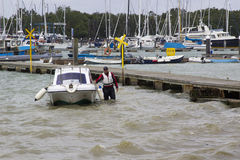 Un dueño del barco que trae su pequeño barco de la fibra de vidrio hacia la orilla en Warsash, Hampshire a un remolque que espera fotografía de archivo