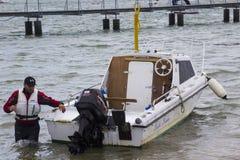 Un dueño del barco que trae su pequeño barco de la fibra de vidrio hacia la orilla en Warsash, Hampshire a un remolque que espera Fotografía de archivo libre de regalías