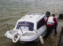 Un dueño del barco que trae su pequeño barco de la fibra de vidrio hacia la orilla en Warsash, Hampshire a un remolque que espera foto de archivo