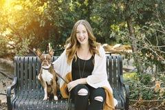Un dueño del perro se sienta con su perro en una sonrisa feliz del banco de parque imágenes de archivo libres de regalías