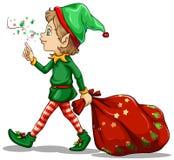 Un duende joven que arrastra un saco de regalos Foto de archivo libre de regalías