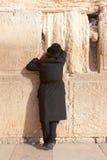 Un ebreo ortodosso religioso prega alla parete lamentantesi Fotografia Stock