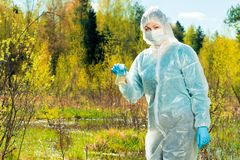 un ecologista del especialista con un frasco de agua de una charca del bosque conduce fotografía de archivo