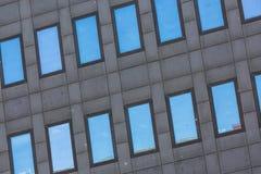 Un edificio alto grigio scuro con le finestre di vetro riflettenti Immagine Stock Libera da Diritti