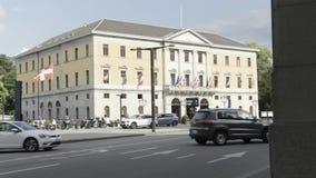 Un edificio con muchas banderas en una calle muy transitada con los coches móviles, embajada en Suiza acci?n Una calle con la con almacen de metraje de vídeo