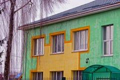Un edificio con una pared verde, las ventanas y el abedul en la yarda Imagenes de archivo