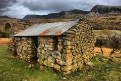Un edificio de piedra viejo con el tejado del metal delante de la cordillera de los idris del cadair en snowdonia Imágenes de archivo libres de regalías