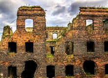 Un edificio destrozado por la guerra del ladrillo rojo, ventanas rotas, cielo melancólico El concepto de las consecuencias de la  Imágenes de archivo libres de regalías