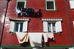 Un edificio rojo y ventanas con el lavadero que cuelga para secarse foto de archivo