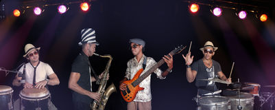 Un'effettuazione dei quattro musicisti isolata sopra indietro Fotografia Stock