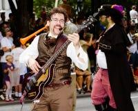 Un ejecutante del musical juega para la muchedumbre en el desfile Imágenes de archivo libres de regalías