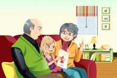 Abuelos y lectura del grandaughter Fotografía de archivo