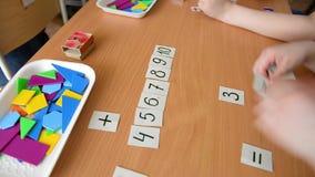 Un ejemplo matemático El niño lleva a cabo una figura de papel Solución de problemas matemática en escuela primaria almacen de video