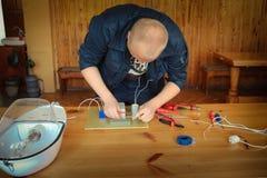 Un electricista del hombre que trabaja trabajos, recoge el circuito eléctrico de una lámpara de calle blanca grande con los alamb fotos de archivo libres de regalías