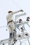 Un electricista está reparando el alambre en polo de la energía eléctrica Foto de archivo