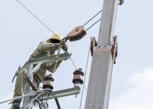 Un electricista que sube en eléctrico está reparando al prisionero de guerra eléctrico Foto de archivo libre de regalías