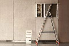 Un electricista vino a un espacio de oficina reparar electricidad en un cuarto Escalera de mano usada para la reparación foto de archivo libre de regalías