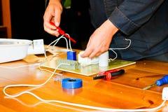 Un elettricista dell'uomo che lavora gli impianti, raccoglie il circuito elettrico di grande lampada di via bianca con i cavi, un fotografie stock